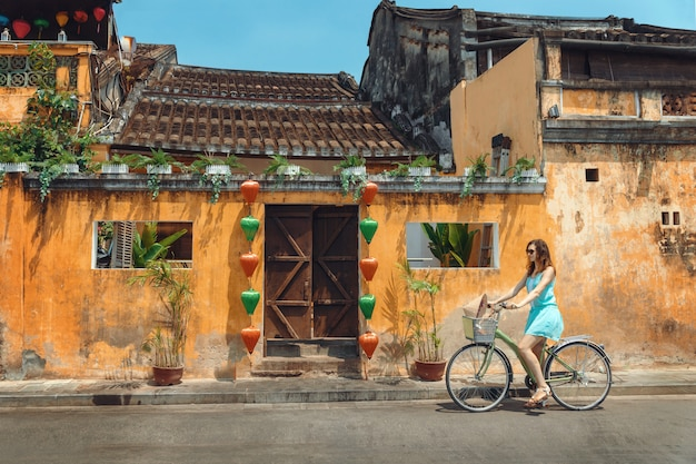 A young woman tourist  in a blue short dress rides a bicycle along the street of the vietnamese tourist city of hoi an. cycling through the old town of hoi an