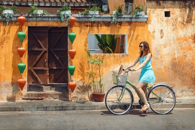 A young woman tourist  in a blue short dress rides a bicycle along the street of the vietnamese tourist city of hoi an. cycling through the old town of hoi an.