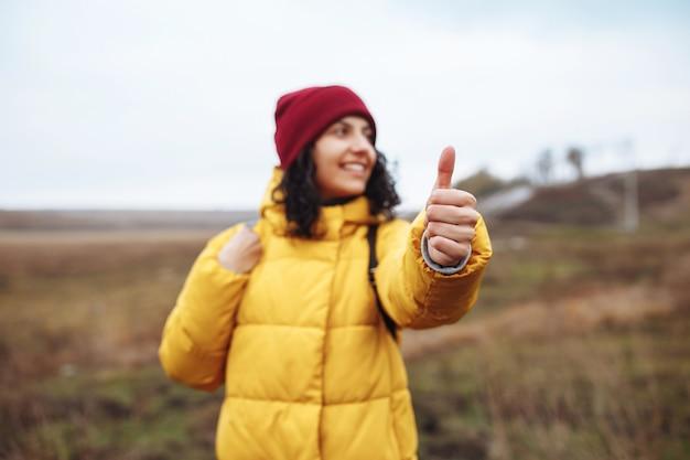 若い女性の観光客は、街から遠く離れた冬の道で車をキャッチします。親指を上に向けます。黄色のジャケット、バックパック、赤い帽子をかぶった女性。