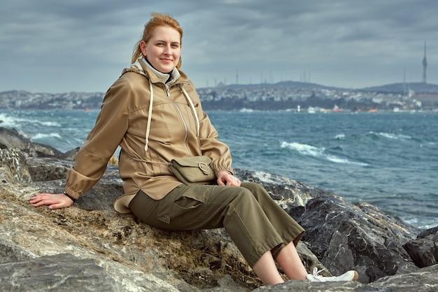 따뜻한 옷을 입고 젊은 여자 관광, 골든 혼 베이 근처 해안 바위에 앉아