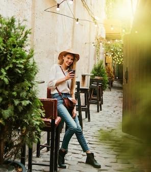 ヴィンテージスタイルの屋外カフェでコーヒーを楽しむ若い女性観光客