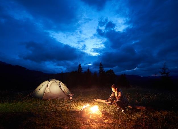 아름 다운 저녁 흐린 하늘 아래 불타는 캠프 파이어 및 조명 된 관광 텐트 근처에 앉아 산에서 야영 밤을 즐기는 젊은 여성 관광객. 관광, 야외 활동 개념