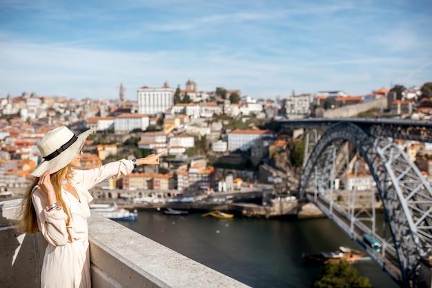 ポルト市、ポルトガルの有名な橋と美しい街並みの背景を楽しむ若い女性観光客