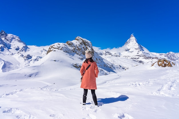 Young woman tourist enjoying with snow mountain matterhorn peak in winter day, zermatt, switzerland.