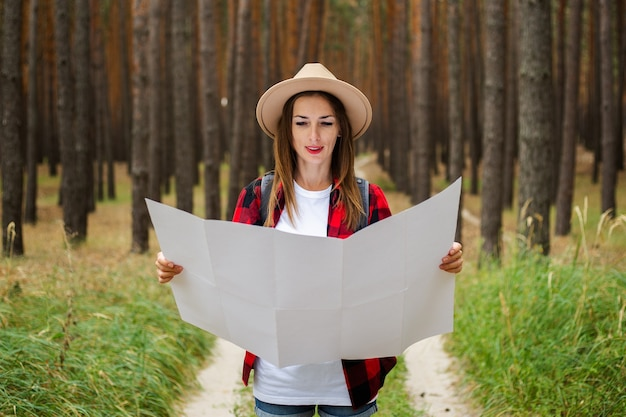 Young woman tourist in a hat, red plaid shirt holds a map of the area in the forest.