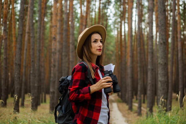 Young woman tourist in a hat, red plaid shirt holds a map and binoculars in the forest.