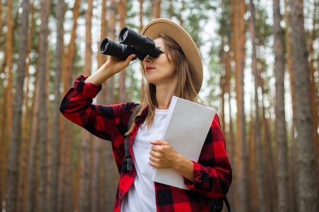 Young woman tourist in a hat and red plaid shirt holds a map and looks through binoculars in the forest.