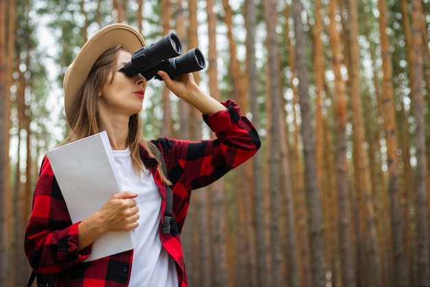 Young woman tourist in a hat and red plaid shirt holds a map and looks through binoculars