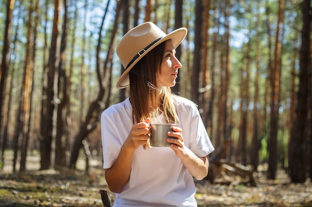 Young woman tourist in hat and t-shirt drinks tea or water during a halt in the forest.
