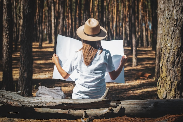 Young woman tourist in a hat and a t-shirt sits on a log and looks at a map during a halt in the forest. back view.
