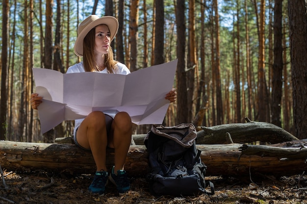 Young woman tourist in a hat and a t-shirt sits on a log and looks at a map during a halt in the forest.