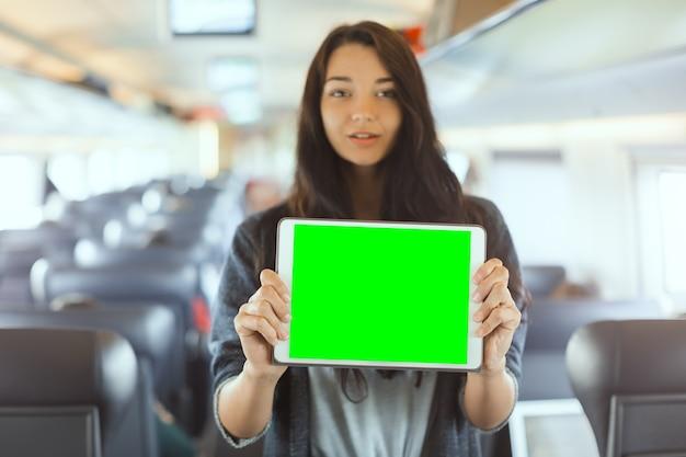 電車で旅行中にタブレットコンピューターを保持している若い女性の観光客。旅行アプリケーションのコンセプト