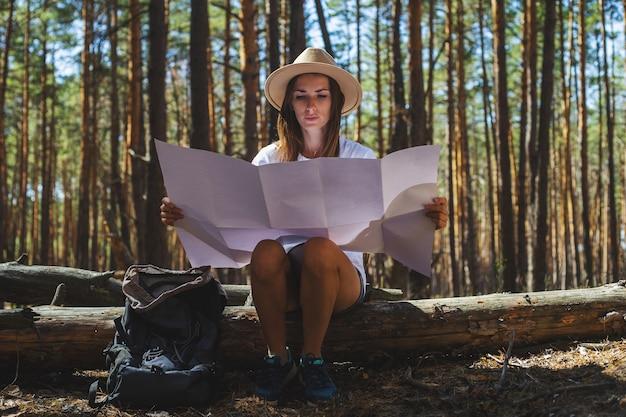 모자와 티셔츠에 젊은 여자 관광은 로그에 앉아서 숲에서 중지하는 동안지도를 본다.