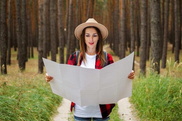 帽子をかぶった若い女性の観光客、赤い格子縞のシャツは森の中の地域の地図を保持しています。