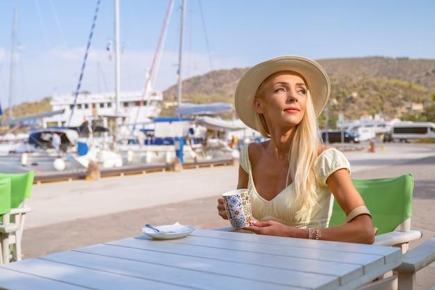 帽子をかぶって、ポロスマリーナベイギリシャでお茶を飲む若い女性の観光客
