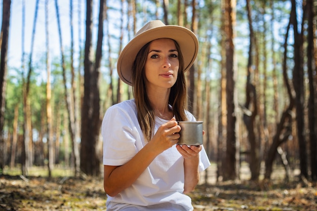 Молодая женщина-турист в шляпе и футболке пьет чай или воду во время остановки в лесу.