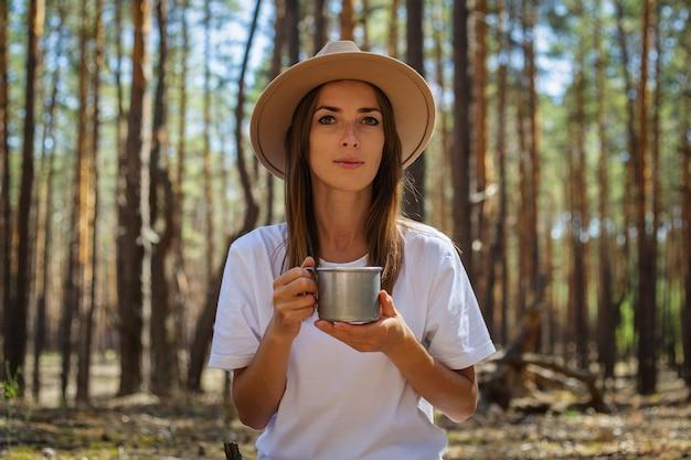 모자와 티셔츠를 입은 젊은 여성 관광객은 숲에서 쉬는 동안 차나 물을 마신다.