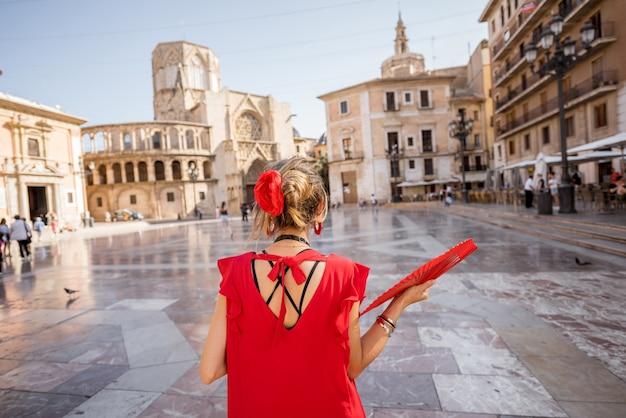 スペイン、バレンシア市の中央広場に立って赤いドレスを着た若い女性観光客