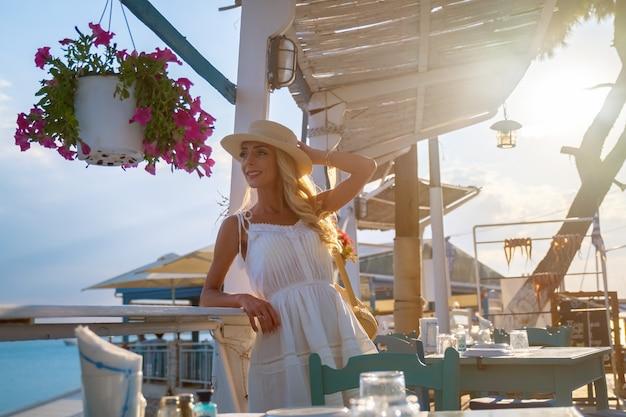 エルミオニマリーナギリシャのカフェに座っている麦わら帽子の若い女性観光客