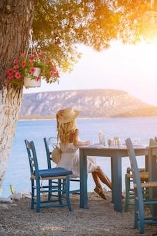 エルミオニギリシャの海の景色を望む崖のカフェに座っている麦わら帽子の若い女性観光客