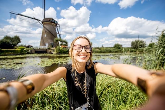 Молодая туристка делает селфи фото на фоне красивого пейзажа со старыми ветряными мельницами в нидерландах