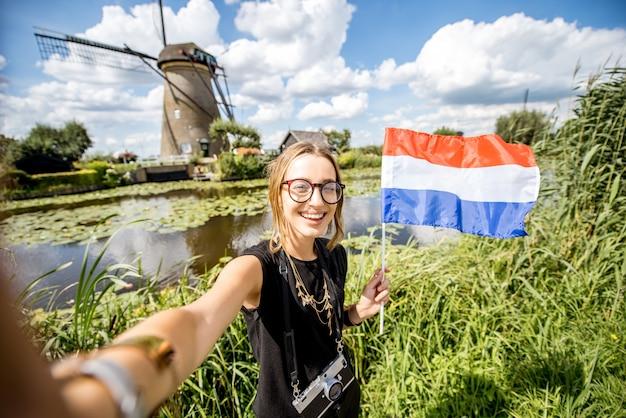 Молодая туристка делает селфи фото с голландским флагом, стоящим на фоне красивого пейзажа со старыми ветряными мельницами в нидерландах