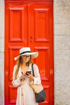 赤いレトロなスタイルのドアの背景に若い女性観光客
