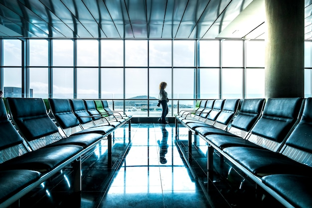 Young woman tourist people walking at the airport mirrored on the clean floor and looking outside the window