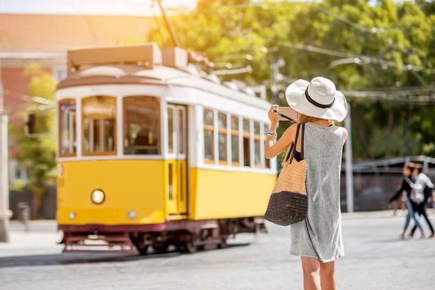 ポルトガルのリスボン市を旅する有名なレトロな黄色の路面電車を撮影する若い女性の観光客