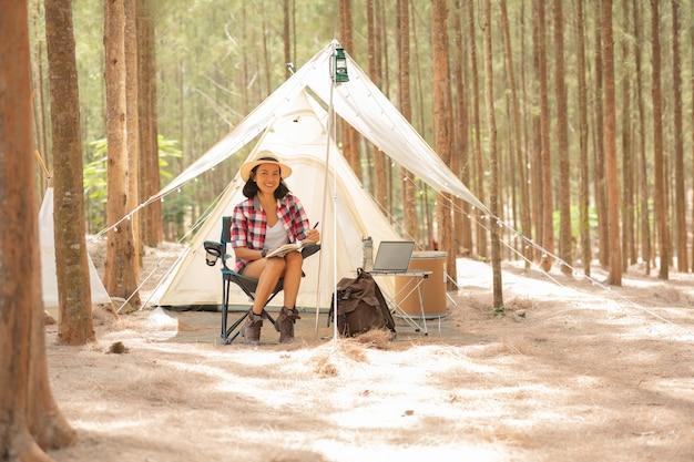 テントの近くに座って本を読んでいる若い女性の観光客。人とライフスタイルのコンセプト。旅行と冒険のテーマ。女性の観光客の肖像画。
