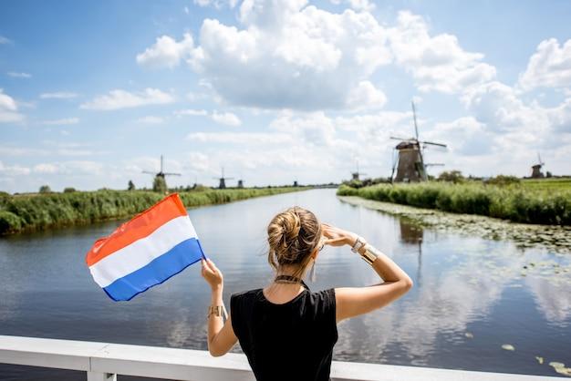 Молодая женщина-турист, стоящая с голландским флагом, наслаждаясь прекрасным видом на красивый пейзаж со старыми ветряными мельницами в нидерландах