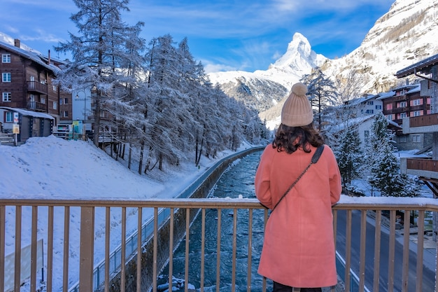 Young woman tourist standing looking view in front of mountain matterhorn peak, zermatt village, switzerland.