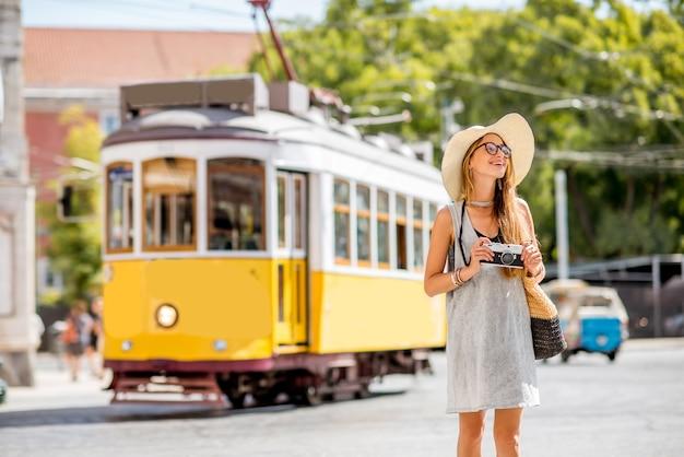 ポルトガル、リスボン市を旅行する有名なレトロな黄色の路面電車の近くに立っている若い女性の観光客