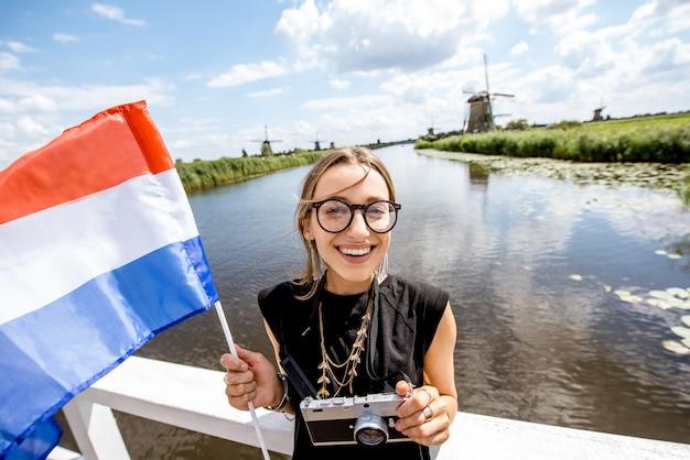 Молодая женщина-турист, стоящая с голландским флагом на фоне красивого пейзажа со старыми ветряными мельницами в нидерландах