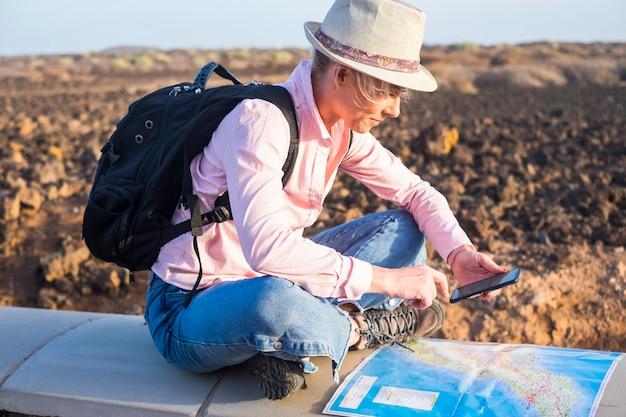 若い女性の観光客がバックパックを持って旅行し、携帯電話技術で地図とインターネットを読んで次のステップを探しています-世界を探索して楽しむためのハイカーとトレッカーの代替の孤独な休暇-無料