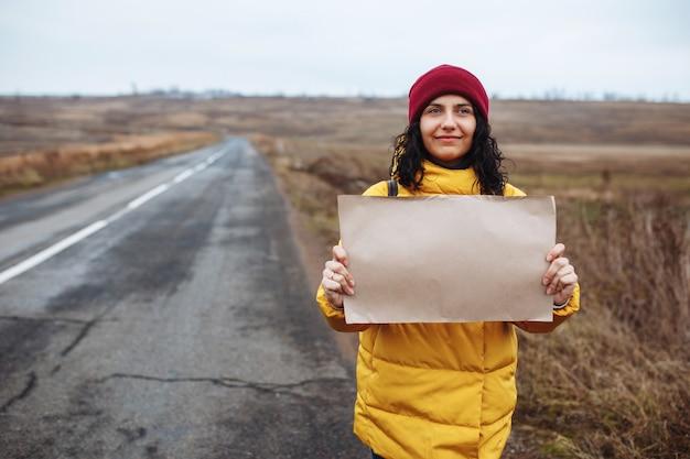 黄色いジャケットと赤い帽子をかぶった若い女性の観光客は、空の冬の道の脇にポスターの白紙で立っています。