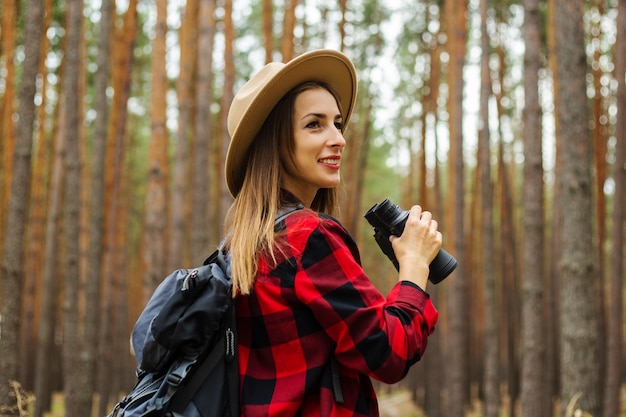 Young woman tourist with backpack, hat and red plaid shirt holding binoculars in the forest.