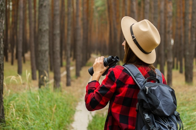 Young woman tourist with backpack, hat and red plaid shirt and looks through binoculars in the forest.