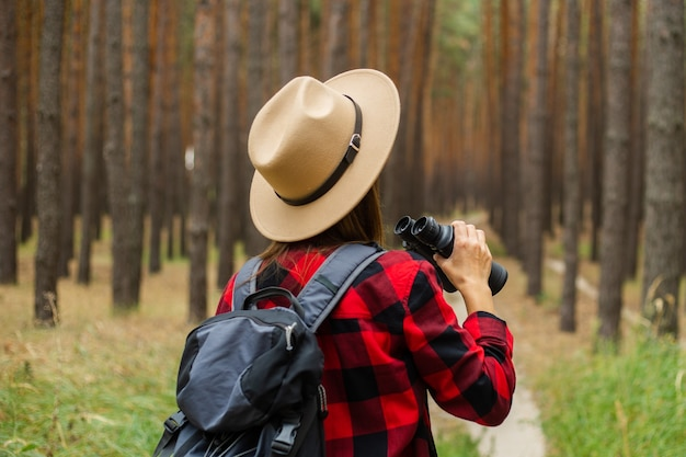 Young woman tourist with backpack, hat and red plaid shirt and looks through binoculars