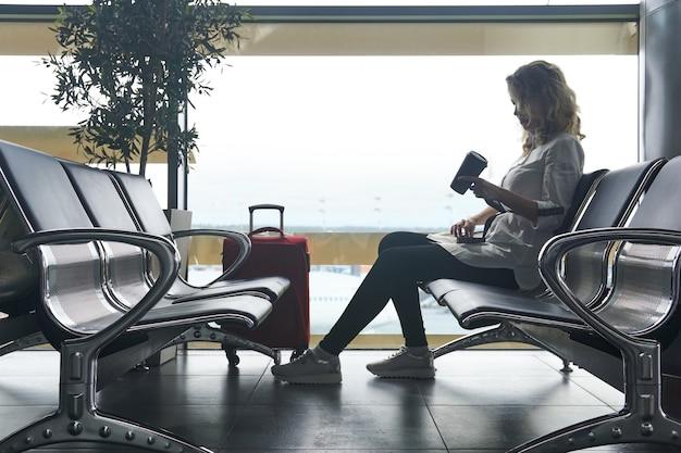 Молодая туристка с чемоданами сидит в зале ожидания аэропорта