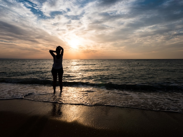 海のビーチの美しい夕日に向かって若い女性。その瞬間を楽しむ