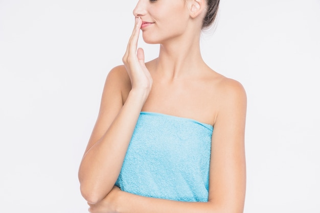 Young woman in towel with hand on lips