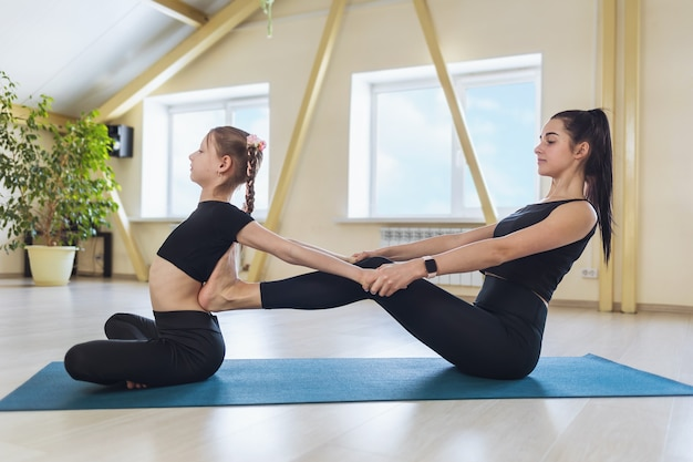 매트에 앉아 척추의 유연성을 위해 운동을 수행하는 데 도움이되는 어린 소녀와 함께 스튜디오에 개인적으로 종사하는 젊은 여성 트레이너