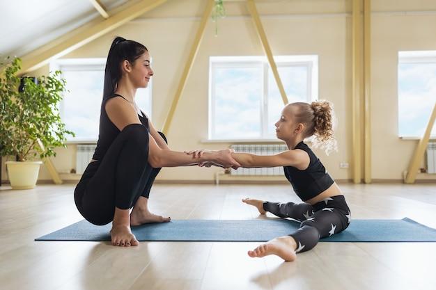 매트에 앉아있는 동안 등과 다리의 근육을 스트레칭하는 운동을 수행하는 데 도움이되는 어린 소녀와 개인적으로 종사하는 젊은 여성 트레이너