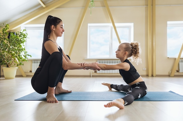 Young woman trainer engaged personally with a little girl helping to perform an exercise to stretch the muscles of the back and legs while sitting on mat