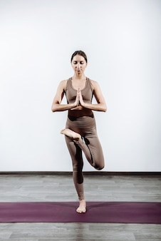 Young woman trainer practicing coaches yoga in the hall standing exercise vrikshasana tree pose