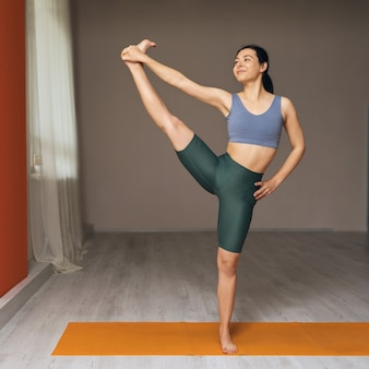 Young woman trainer practicing yoga standing on the mat in the studio performs the exercise uttita hasta padangusthasana 2