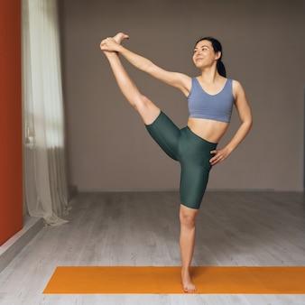 スタジオでマットの上に立ってヨガを練習している若い女性トレーナーがエクササイズを行いますuttitahasta padangusthasana 2