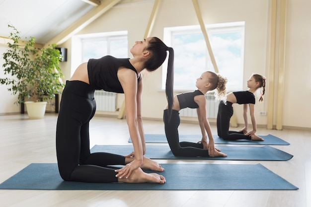 Young woman trainer with two little students perform ushtrasana exercise camel pose