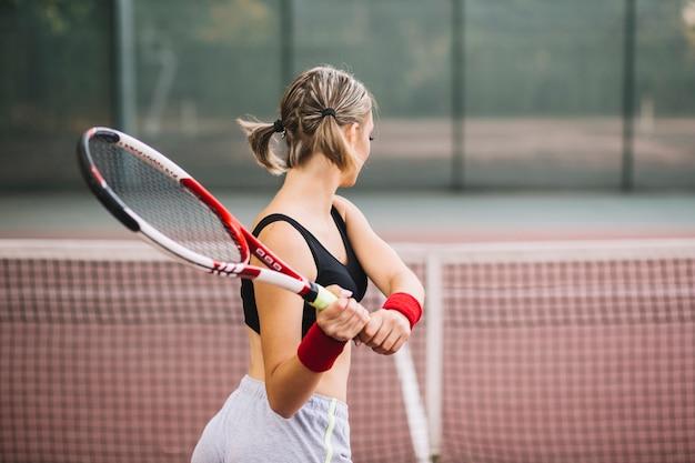 Тренировка молодой женщины по теннису